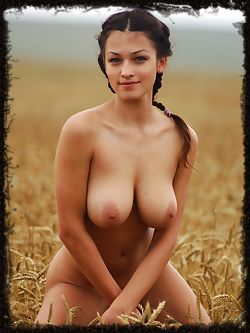 Sofi A shows off her large, natural breasts in a field
