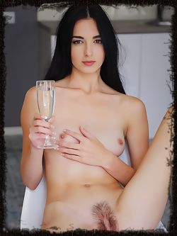 After a glass of sparkling champagne, Benita takes off her t-shirt and spreads her legs wide open to flaunt her exquisite, unshaven pussy.