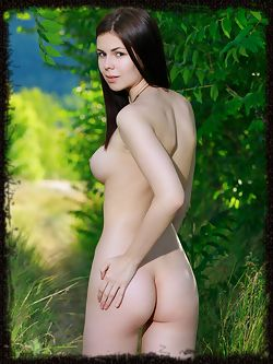 Karolina Young posing in the lush green woods. The deep verdant colors makes her smooth, pale skin stand out, and her cuppable breasts with pink nipples and shaved pussy.