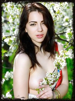 Like a gorgeous woodland nymph, Sivilla's beauty and feminine allure stands out against the flowers and trees around her.