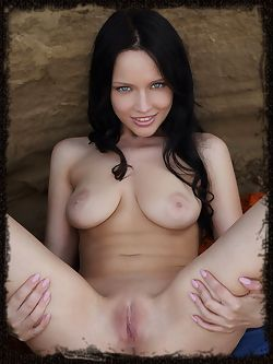 Marica A is squishing her feet in the wet sand as she plays naked amongst the rocks